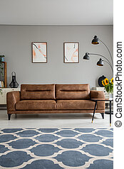 Blue patterned carpet and leather sofa in grey living room interior with posters and lamp. Real photo
