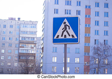 Blue pedestrian crosswalk sign on a street