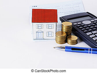 Blue pen with coins stack and paper house and calculator on saving book
