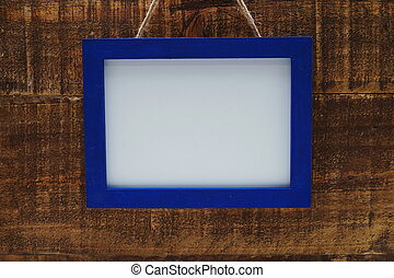 Blue photo frame on grunge wooden background