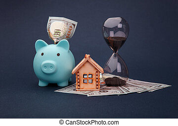 Blue piggy bank with wooden model of house, hourglass and money banknotes on blue background. Savings money for buy house