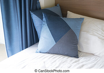 Blue pillows on sheets bed with blue curtain