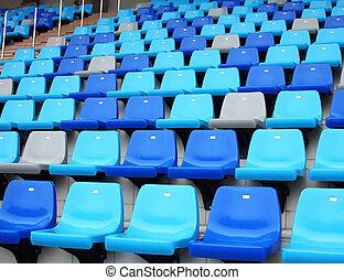 blue plastic old stadium seats on concrete steps