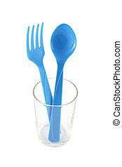 Blue plastic utensil in glass on white background.