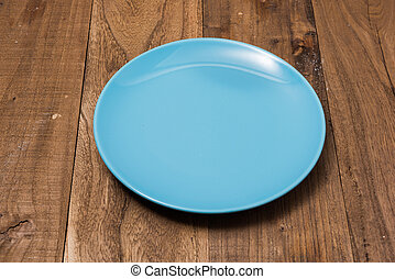 Blue Plate on brown wooden background side view