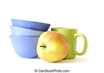 blue plates, green cup and yellow apple