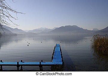 Blue pontoon and view of annecy lake and mountains on winter morning