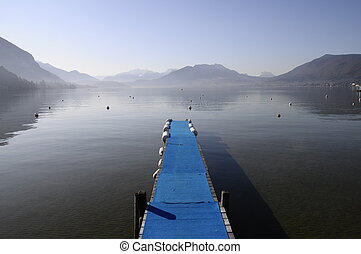 Blue pontoon and view of annecy lake and mountains on winter...