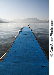 Blue pontoon on lake annecy on morning with vertical view, France