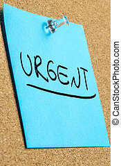 Urgent - Blue post it paper pinned to a cork bulletin board ...