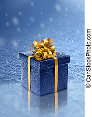 Blue present box on ice in snowfall