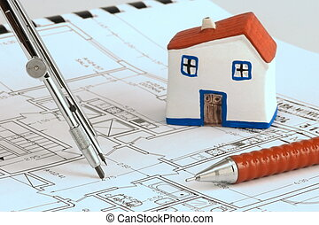Blue print with miniature model house, compass and pencil