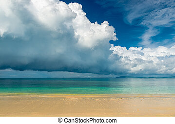 Blue rain clouds hover over the calm sea of Thailand