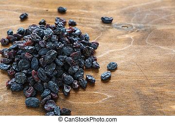 blue raisins on wooden background