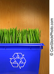 Blue recycle bin with grass inside