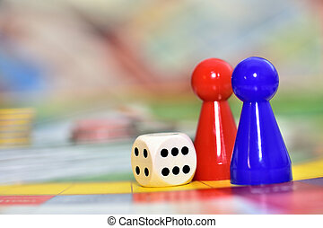 Blue, red play figures and dice on the board game.