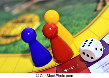 Blue, red, yellow play figures and dice on the board game