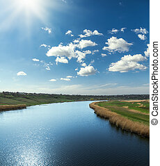 blue river and sky with clouds and sun
