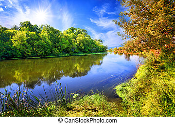 Blue river or lake with bright green trees on the shore