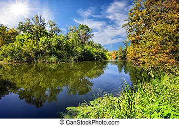Blue river or lake with green trees on the shore
