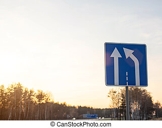 Blue road sign on sky background with sunny sunset narrowing the road to the right. Concept of warning signs about lane change