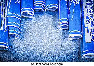 Blue rolled engineering drawings on metallic background construc