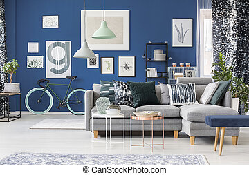 Blue room with abstract patterns on pillows, curtains and posters on wall