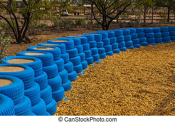 Blue Rubber Tires Used As Bumpers For Small Children at Desert Playground