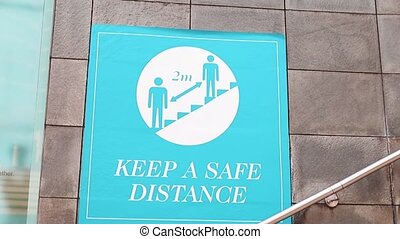 FHD view of a blue sign on a wall that requests people to 'keep a safe distance' for safety measures due to covid 19