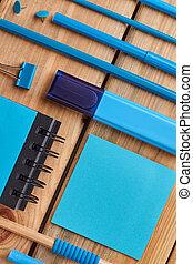 Blue school supplies on wooden background.