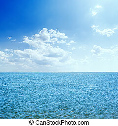 blue sea and clouds in sky with sun