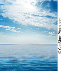 blue sea and clouds with sun over it in sky