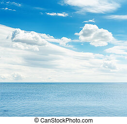 blue sea and sky with white clouds over it