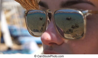 blue sea is reflected in the mirror glasses - close up of...