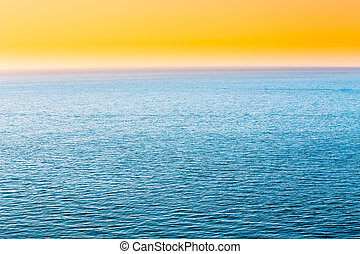 Blue Sea Or Ocean And Yellow Clear Sunset Or Sunrise Sky Background