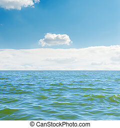 blue sea, sky and white clouds over it