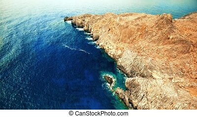 Blue sea, waves breaking in cliffs at shore - flying above...