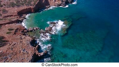 Blue sea, waves breaking in cliffs at shore