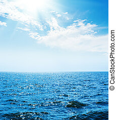 blue sea with waves and sky with sun and clouds over it