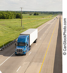 Blue Semi Truck Trailer Rig Hauls Freight on Divided Highway...