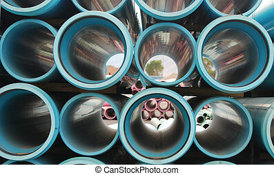 Blue sewer pipes stacked together with pink pipes in the background.