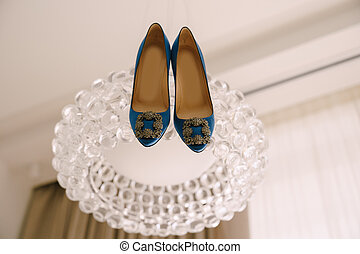 Blue shoes of the bride with a buckle on a glass chandelier.