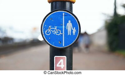 Round blue sign on pole with images of people and a bicycle indicating the pedestrians and cyclists paths. Road sign with pedestrians in the background. Road safety signs