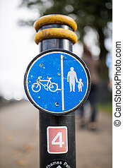 Blue sign on a pole indicating the pedestrians and cyclists paths