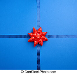 blue silk ribbon crossed on a dark blue background in the middle of a red bow