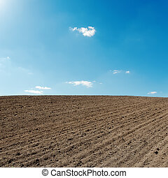 blue sky and black agriculture field