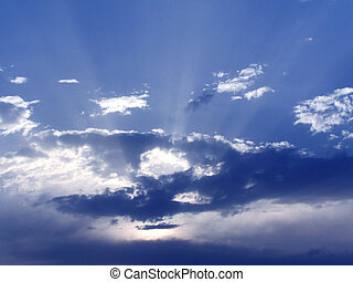 Blue sky and clouds - Rays of light on a cloudy sky