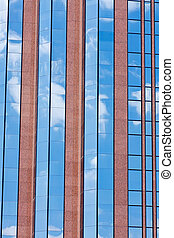 Blue Sky and Clouds Reflected in Glass and Red Stone Building