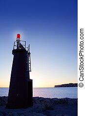 Blue sky and red lighthouse glowing on sunset sea