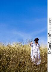 Blue sky and yellow meadow field with wheats.Beautiful,graceful,posing girl stand in field.Goddess, graceful girl in the field with blue sky,white dress, meadow,sunny field. Exquisite, stunning,striking girl poses, raises hands up in the field with flowers, dry grass, cones, grain and looks up.
